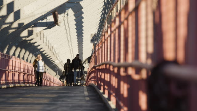 closeup shot of bikers passing on a new york city bike path - williamsburg bridge - 4k - williamsburg bridge stock videos and b-roll footage