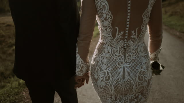 close-up shot of bride and groom walking in countryside and having romantic time while sun sets. - abito da sposa video stock e b–roll