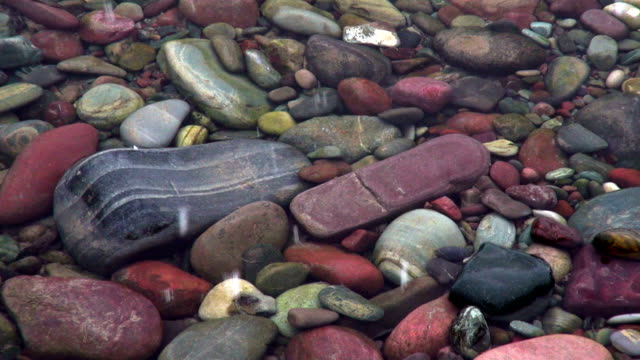 closeup shot of brightly color rocks on river bottom with snow flakes hitting waters surface. - glacier national park us stock videos and b-roll footage
