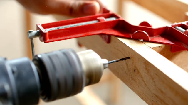 close-up shot of carpenter drilling a hole on wood beam of table - instruction manual stock videos and b-roll footage