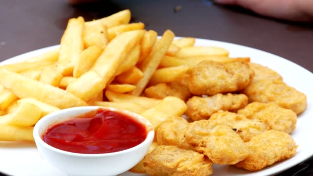 vídeos de stock, filmes e b-roll de close-up do tiro das crianças mãos que mergulham a pepita de galinha na ketchup - unhealthy eating