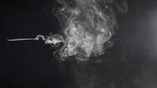 close-up shot of cigarette smoke on black background. - cigarette stock videos & royalty-free footage