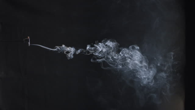 close-up shot of cigarette smoke on black background. - dipendente video stock e b–roll