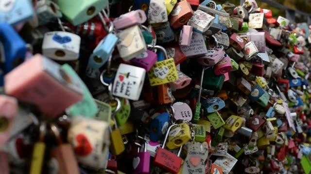 vídeos de stock, filmes e b-roll de close-up shot of colorful locks at the top of n seoul tower - escrita ocidental