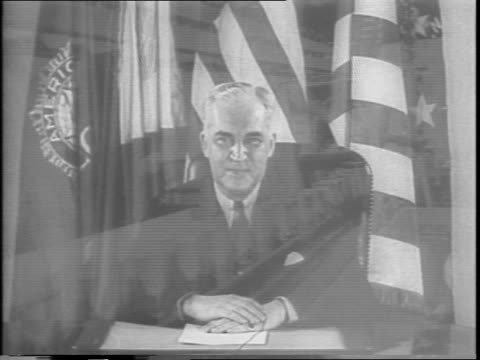 closeup shot of commissioner of war manpower board paul mcnutt seated at a desk in front of flags / he discusses the average american duty to can - anno 1943 video stock e b–roll