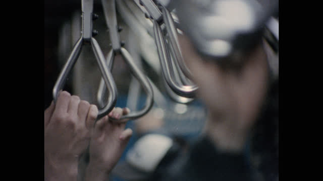 close-up shot of commuter's hands holding straphanger while traveling by subway train, new york city, new york state, usa - interno di veicolo video stock e b–roll