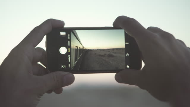 close-up shot of cropped hands photographing landscape against sky during sunset through smart phone while traveling in train - swakopmund, namibia - photographing video stock e b–roll