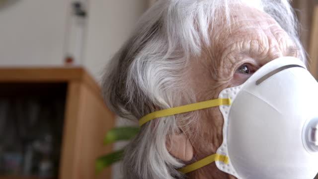 vidéos et rushes de plan rapproché de la femme âgée âgée âgée caucasienne désemparée regardant par la fenêtre sentiment de solitude portant un masque protecteur n95 pour empêcher la propagation du coving sras ncov 19 coronavirus grippe porcine h7n9 maladie grippale - sécurité sociale