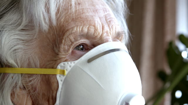 close-up shot of distraught elderly senior caucasian woman looking out the window feeling loneliness wearing an n95 protective face mask to prevent the spread of covid sars ncov 19 coronavirus swine flu h7n9 influenza illness during cold and flu season - social services stock videos & royalty-free footage