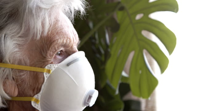 close-up shot of distraught elderly senior caucasian woman looking out the window feeling loneliness wearing an n95 protective face mask to prevent the spread of covid sars ncov 19 coronavirus swine flu h7n9 influenza illness during cold and flu season - social issues stock videos & royalty-free footage