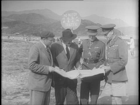Closeup shot of Ernest Hemingway and Arthur Menken shown plans by officials in military area / two shots of the Hong Kong defensive forces drill on...