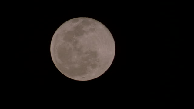 Close-up shot of full moon in clear dark sky.