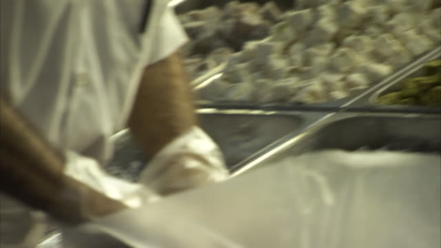 stockvideo's en b-roll-footage met close-up shot of gloved hands arranging turkish sweets at istanbul's grand bazaar, turkey. - turks fruit