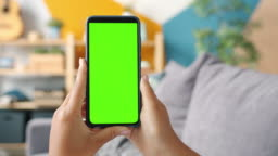 Close-up shot of green screen template smartphone in female hands at home