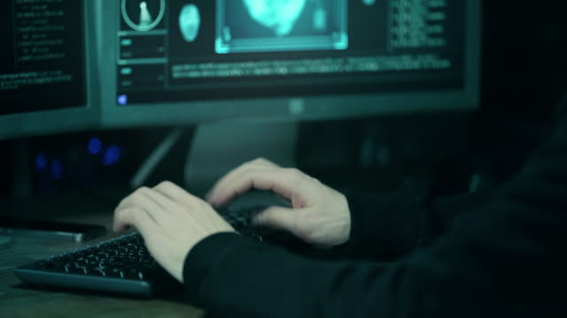 close-up shot of hacker using keyboard. there is coffee cups and computer monitors with various information. - hacker stock videos and b-roll footage