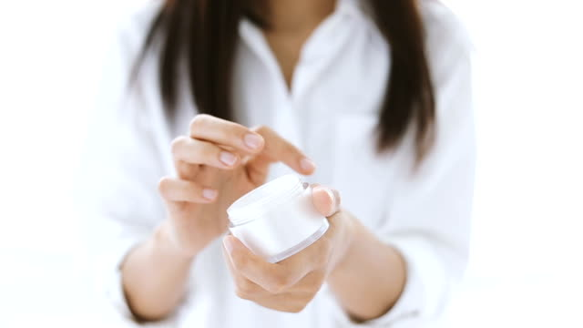 closeup shot of hands applying moisturizer. beauty woman holding a glass jar of skin cream. shallow depth of field with focus on moisturizer - mole skin stock videos and b-roll footage