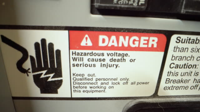 close-up shot of high voltage danger warning sign sticker on a 20-amp electrical breaker panel from a commercial building install - high voltage stock videos & royalty-free footage