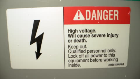 close-up shot of high voltage danger warning sign sticker on a high voltage indoor transformer from a commercial building install - high voltage sign stock videos & royalty-free footage