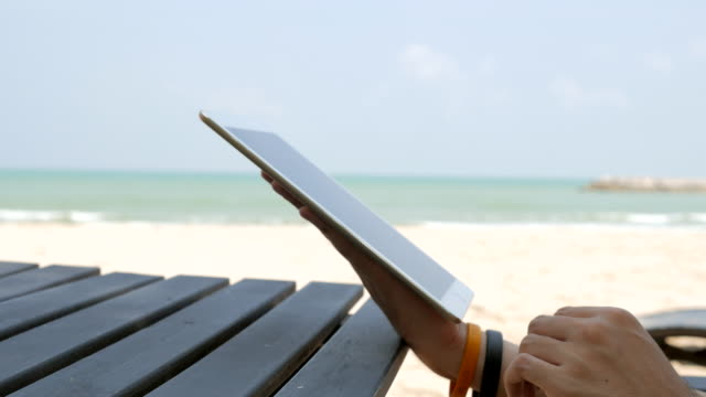 Close-up shot of man hands typing on tablet computer on the beach