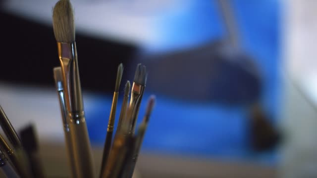 close-up shot of paintbrushes in the foreground while an artist wearing protective gloves applies blue paint to a canvas using a large paintbrush - craftsperson stock videos & royalty-free footage