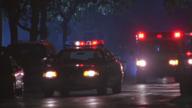 Close-up shot of police vehicles moving on a street at night.