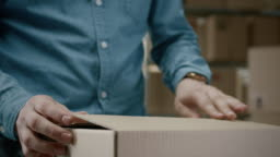 Close-up Shot of Professional Warehouse Worker Checks and Seales Cardboard Box Ready for Shipment. In the Background Rows of Shelves with Cardboard Boxes with Ready Orders.