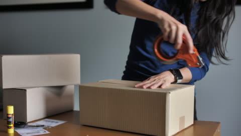 närbild skott av professionella lagerarbetare förpackning kartong redo för leverans - etikett bildbanksvideor och videomaterial från bakom kulisserna