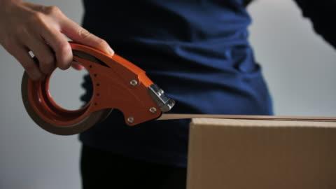 stockvideo's en b-roll-footage met close-up shot van professionele magazijnmedewerker verpakking kartonnen doos klaar voor verzending - merchandise
