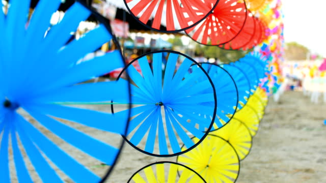 close-up shot of rotating colorful windmill toy in row - girandola video stock e b–roll