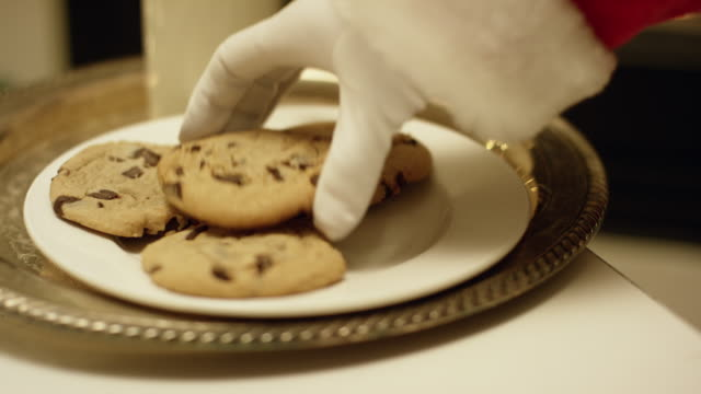 close-up shot of santa claus' gloved hand picking up a chocolate chip cookie from a tray with a glass of milk on it with a fireplace in the background on christmas eve - chocolate chip cookie stock videos and b-roll footage