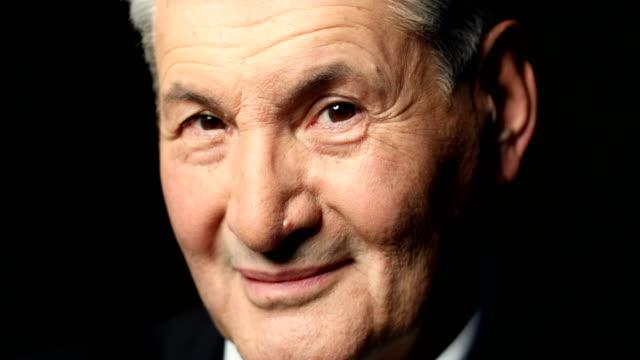stockvideo's en b-roll-footage met close-up shot van senior zakenman glimlachen - formeel portret
