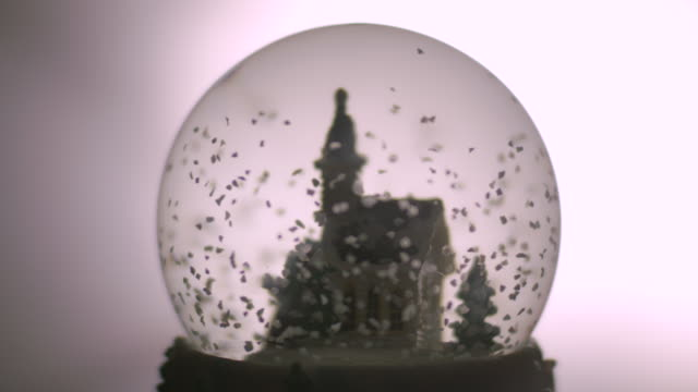 close-up shot of 'snow' swirling round a plastic church before settling to the base of a snowglobe. - palla dell'albero di natale video stock e b–roll