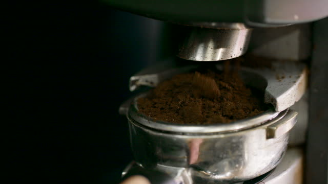 close-up shot of someone filling a portafilter (espresso machine) with coffee grounds while making coffee - grinding stock videos & royalty-free footage
