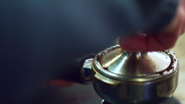 close-up shot of someone tamping (pressing) coffee grounds in a portafilter (espresso machine) - italian culture stock videos & royalty-free footage