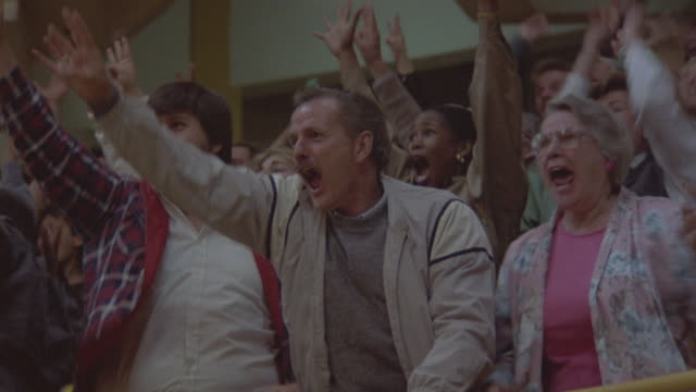Close-up shot of spectators cheering during a game.