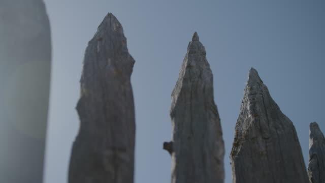 vidéos et rushes de close-up shot of spikes on the top of a fortress wall - poteau en bois