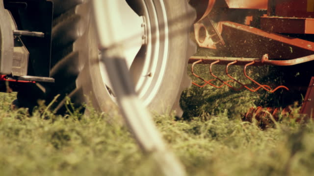 close-up shot of the bottom of a hay baler as it gathers hay from the ground - hay baler stock videos & royalty-free footage