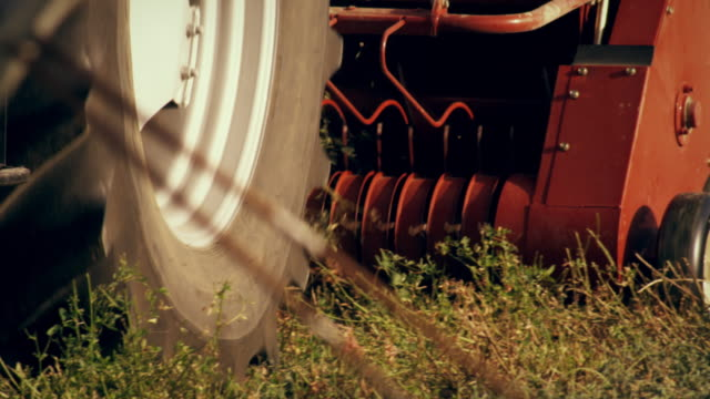 close-up shot of the bottom part of a tractor as it gathers hay - プロボ点の映像素材/bロール