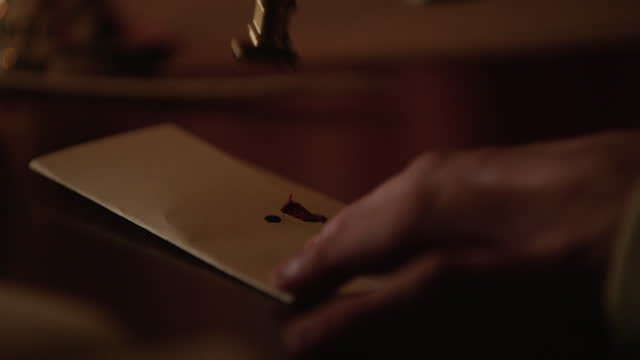vídeos de stock e filmes b-roll de close-up shot of the hands of a man melting wax and sealing a letter - século xviii