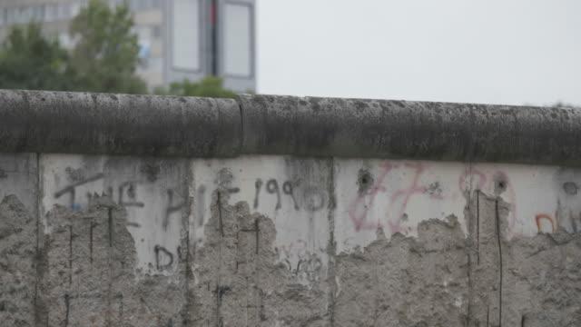 vídeos y material grabado en eventos de stock de close-up shot of the preserved remains of the berlin wall outside of the topography of terror museum - pared de cemento