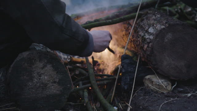 stockvideo's en b-roll-footage met close-up shot of two persons making a fire - buitensport