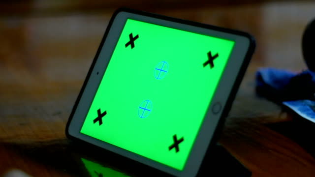 Close-up shot of Using tablet with green screen on wood table
