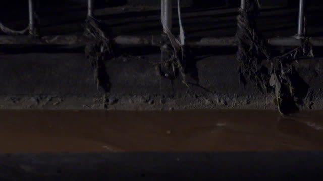 close-up shot of water flowing past dirty railings in a sewer in austria. - sewage stock videos and b-roll footage