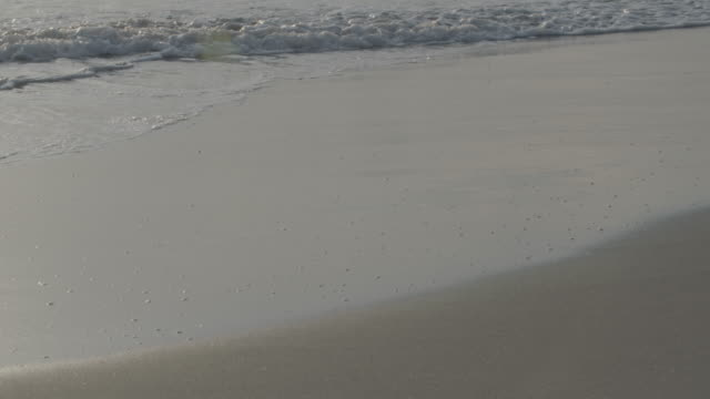 Close-up shot of waves reaching a shore