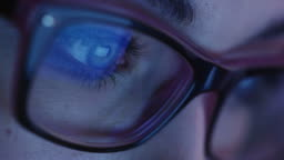 Close-up shot of woman eye in glasses staring at a working tablet screen in the dark.