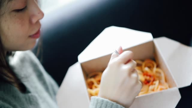 close-up shot of young woman eating takeaway pasta - fast food点の映像素材/bロール