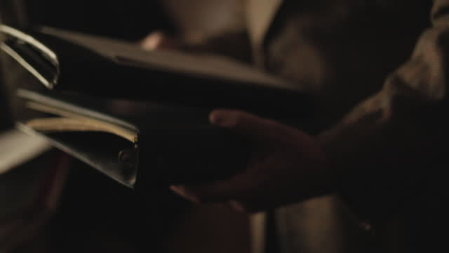 close-up shot reenactment of the hand of a man holding a leather binder during the 1980s - document stock videos & royalty-free footage