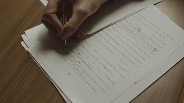 vidéos et rushes de close-up shot reenactment of the hand of a man writing notes on a document during the 1980s - contrôle