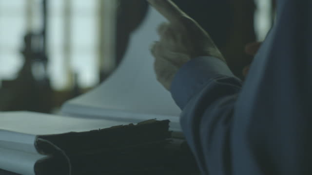 close-up showing the hand of a middle-aged man as he looks through a stack of historical papers. - stack stock videos and b-roll footage