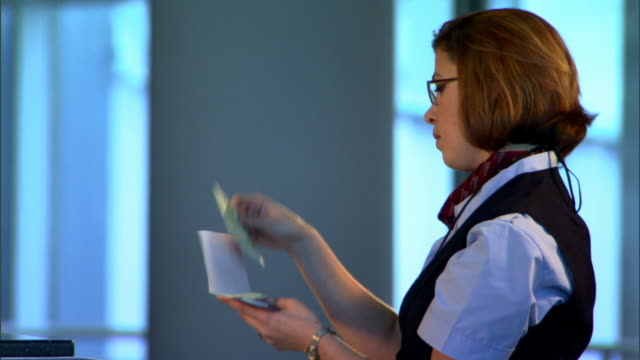 close-up side view of a flight attendant checking a ticket and returning it to the unseen customer. - airline check in attendant stock videos and b-roll footage